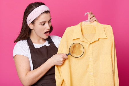 Closeup portrait of woman holds magnifier and shirt with spot in hand. Attractive lady wears white shirt and brown apron looks surprised, stands with opened eyes. Copy space for your advertisment. Stock Photo