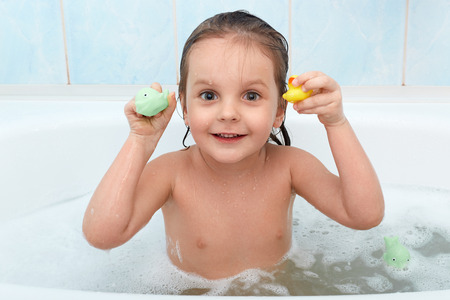 Little baby girl holding toy in hands taking bath, plays in water with duck and dolphin. Adorable child being photographed while relaxing with foam in bathroom. Hygiene and health care concept.