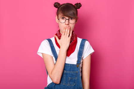 Image of surprised dark haired teenager with funny banches, covers mouth with hand, wears t shirt, overalls, glasses and bandana, looks with wide open eyes, hears shocking news, isolated on pink wall.