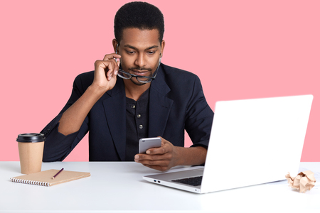 Close up portrait of African American businessman checked email on his smart phone, sits in front of laptop, working online, has serious facial expressions Dark skinned male earns money online.