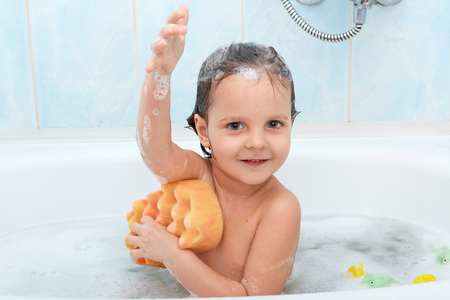 Cheerful positive adorable small child taking bath and washing herself with yellow sponge, expresses pleasant emotions, being glad to relax, isolated on blue wall in bathroom. Hygiene concept.