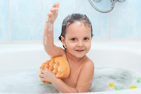 Fröhliches positives entzückendes kleines Kind, das ein Bad nimmt und sich mit gelbem Schwamm wäscht, drückt angenehme Emotionen aus, freut sich, sich zu entspannen, isoliert auf blauer Wand im Badezimmer. Hygienekonzept.