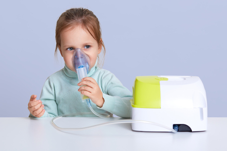 Close up portrait of charming cute small girl uses nebulizer mask for inahlation, has respiratory disease, sits at white desktop, isolated over white background. Little girl cures cough or pneumonia