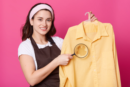 Studio shot of pleasant looking housewife with pleasent look, wears white hair band, casual t shirt, and brown apron, poses against pink background. Beautiful woman shows large spot with magnifier. Archivio Fotografico