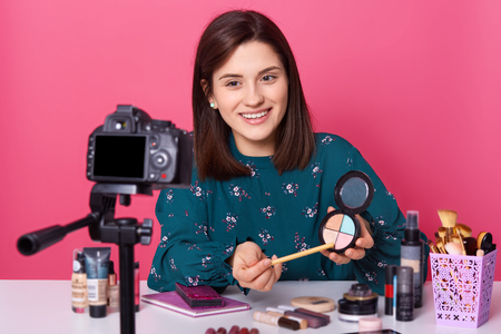 Close up portrait of young woman sits in front of camera, has pleasent expression, surrounded with beauty products. Charming female holds eyeshadow. Vlogger makes video isolated over pink background. Stockfoto