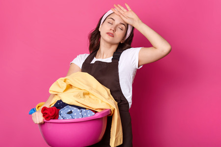 Tired busy European woman holds basin with dirty clothes, keeps eyes closed, prepares for washing, wears headband, apron and t shirt, models over rosy studio wall. Emotional housewife does households Imagens