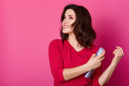 Beautiful girl laying fixes using hairspray, prepares for dating with boy friend, makes new hairstyle. Smilling brunette poses isolated on pink background, looks aside, holds bottle of moussein hands.