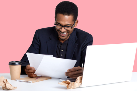 Portrait of cheerful male financier with dark skin, wears glasses, has fan expression, prepares report, drinks coffee, laughing while reads documents isolated over pink background. Business concept.