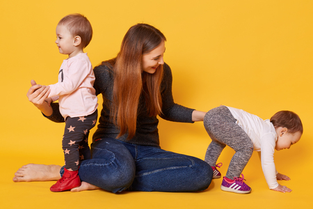 Studio shot of happy family, mommy with her charming and cute twins, mother tries to bring her doughter together and make photo, mom plays with her infants, sisters run away from mamma. Copy space.