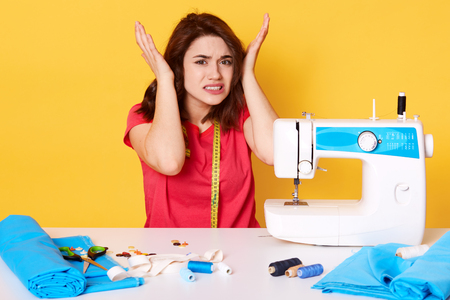 Close up image of unhappy young brunette woman, sits with unpleasent facial expresions near broken sewing machine which works very loud, keeps hands on head, dressed red t shirt, against yellow wall.