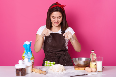 Young woman baker in kitchen, sprinkling white flour on dough, baking delicious coockies, likes homemade pastry, posing isolated over pink background. Copy space for your advertismant or promotion.