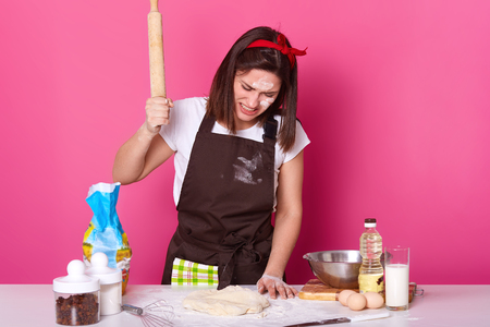 Portrait of young brunette stressed female working in kitchen whole day, preparing homemade pastry, looks tired. beats on dough with wooden rolling pin with anger isolated on rose background.