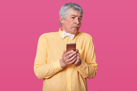 Close up portrait of mature man holding his smart phone in hands, does not know how to make video call, wears yellow shirt and white bowtie. Technology, people, lifestyle and communication concept.