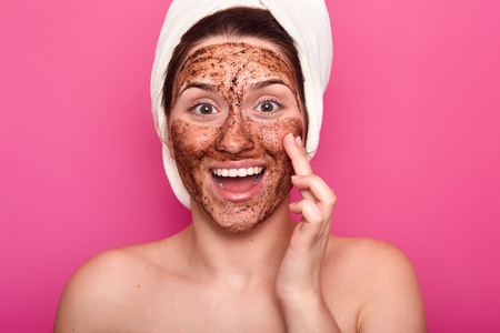 Isolated shot of surprised woman applies mask on face, has happy facial expresion, opens mouth from amezmant, having rest while doing beauty procedures, wears white towel on head. Wellness concept