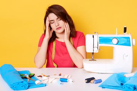 Nahaufnahmeporträt einer dunkelhaarigen jungen frau arbeitet als näherin, näht neues kleid für ihre tochter, sieht müde aus, sitzt in der nähe der nähmaschine und hält die hand auf dem kopf. Nadeln, Faden und Tuch auf dem Tisch. Standard-Bild