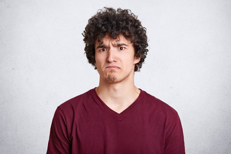 Gloomy bearded guy frowns face, being dissatisfied with results of exames, demands explanation why he looses. Handsome young man with dark curly hair isolated on white background. People and emotions