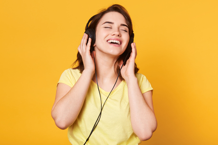Beautiful woman listening to music on yellow background. Charming lady posing with closed eyess, enjoys of listening favourite music, keeps hands on headphones, sings and relaxes. Lifestyle concept.