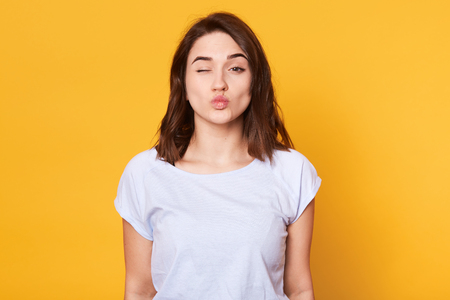 Close up portrait of adorable brunette woman pouts lips and winks, makes grimace, rounds lips for making kiss, isolated over yellow background. Copy space for your advertisment or promotional text.