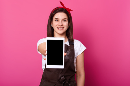 Woman, baker wears brown apron dirty with flour, showing blank empty screen with copy space. Happy Caucasian model poses smiling with digital gadget in her hand, being in good mood, studio shot.