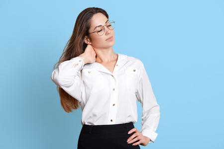 Tired hard working female touches her neck, closes her eyes, enjoys spare time. Satisfied good looking young businesswoman wears formal smart blouse and black skirt, fashionable spectacles.