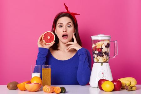 Young and healthy woman has surprising facial expression, holds piece of grapefruit in her hand, isolated over pink background. Large variety of fresh fruit and vegetables on table surface. Foto de archivo