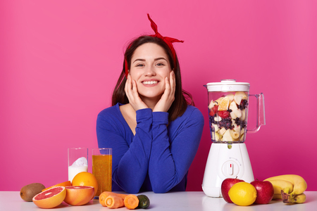 Close up portrait of cute smiling young woman with happy expression, keeps her hands on cheeks, being photographed in photo studio isolated over pink background with lots of fruit and blendrer.