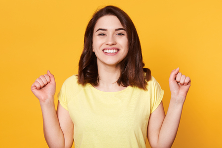 Happy woman dressed casual t shirt, clenching her fists with excitement, celebrating, achieving goal, her dreams come true, posing isolated on yellow background. Success, victory, achievement concept.