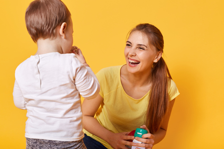 Laughing joyful woman plays with her little cute daughter, spends free time together on the weekends. A young woman is happy to bring up and care her obedient small tiny child. Family concept.