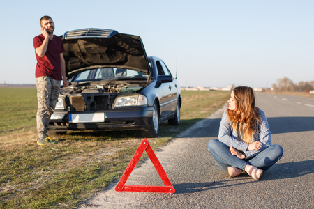 Outdoor shot of couple near his brocken car, red triangle as warning sign, male stands in front of opened hood and calls tow truck, female sits on road with crossed legs, waits solving problem.
