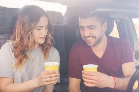 Attractive female and unshaven male couple have coffee break in auto, reach destination wih high speed. Happy family spend time together, travel on weekend, enjoying cool vocation. Travelling concept.