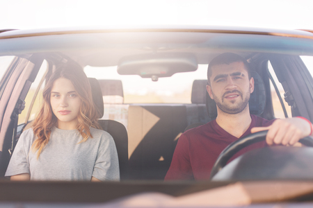 Young man and woman sitting in car, look directly at camera, dressed casually, couple have long trip, spend vacation together, has calm facial expressions. Family has trip or journey by vehicle