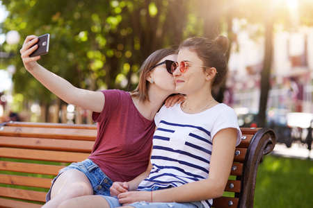 Happy sincere two girls make selfie on the wooden bench sitting in the park. Cheerful young girl kisses her best friend in right cheek while taking photo. Friends are looking forward to see photos. Archivio Fotografico