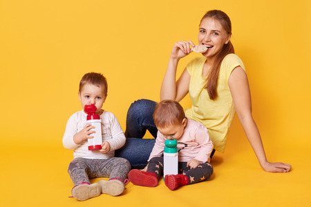 A smiling eating mother takes care of her little funny daughters. Calm adorable babies drink liquid and have relax during their lunch. Family enjoy spending time together. Childcare concept. Archivio Fotografico