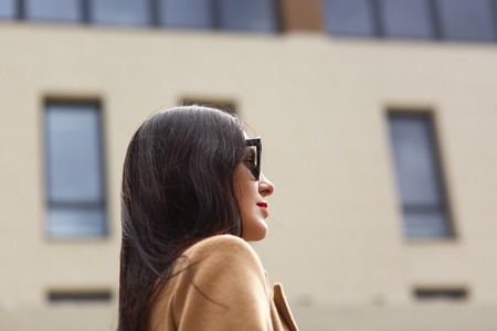 Portrait of beautiful young businesswoman outdoor over blurred street background. Profile of elegant brunette female, wears beige coat and black sunglasses, looking straight ahead. People concept.