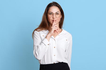 Szczupła Europejka pokazuje gestem milczenia, trzymając palec wskazujący przy ustach, stoi pewnie i pewnie z rozpuszczonymi długimi ciemnymi włosami i szeroko otwartymi niebieskimi oczami. Skopiuj miejsce na reklamę.