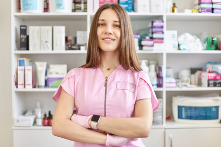 Positive nice young beautician stands in her cabinet with folded hands and pose and looks at camera. Beautician dressed pink gown, lots of drugs on background, specialist of aethetic medicine 写真素材