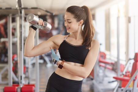 Athletic young woman with simulators on background, holds dumbbell in hand and shows her biceps, looks on her arm, has workout for upper body. Bodybuilding and healthy lifestyle concept. Stockfoto