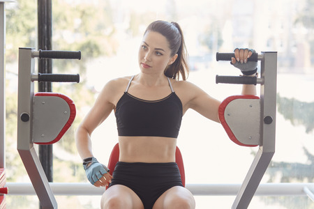 Athletic attractive attentive girl looks aside, sits on training simulator, holds one hand on it, listens to instructions carefully, going to do strength exercises, developing her body muscles. Stock Photo