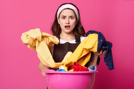 Close up portrait of astonished woman with huge pink basin with fresh clothes and home textile, has shocked facial expression after washing, has some problem with her linen, does not know what to do. Фото со стока - 120936859