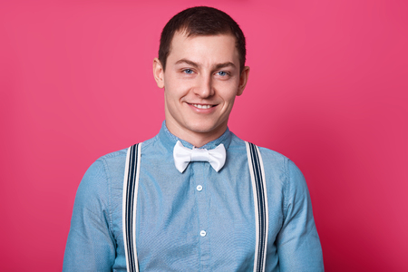 Close up portrait of cheerful joyful black haired guy, isolated over pink studio background. High spirited canty young man wears blue shirt, bow tie, spenders. People, youth, emotions concept.