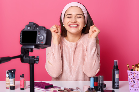 Studio shot of happy smiling woman , sitting with closed eyes, her dream comes true, recording tuorial video at home for vlog, earns money in internet. Blogging, modern technology and people concept.