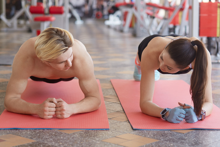 Portrait of muscular couple doing planking exercises on sports mat, doing sit ups, look at each other, work out in gym, tone muscles, has competition, athletic family training together. Sport concept.
