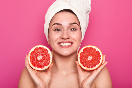 Studio shot of attractive woman with grapefruit in her hands and with white towel on her head, female after taking shower or bath, being in good mood, posing with toothy smile. Skin care concept. 免版税图像