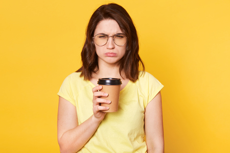 Indoor shot of dark haired girl with upset expression, purses lower lip, holds cup of coffee, wears round glasses, casual t shirt, grimaces her face dislikes taste of beverage, against yellow wall. Standard-Bild - 121070072