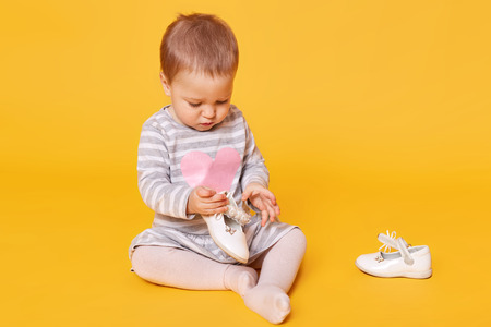 Young little girl in striped dress with pink heart and tights sitting on yellow background in studio and playing with her white shoes. Cute concentrated toddler holds her shoe and looks on it.