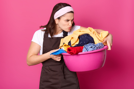 Indoor shot of young tired housewife, doing house chores, smelling dirty clothes, going to wash them, having disgusting facial expression, hates washing process. Household and domestic chores concept.