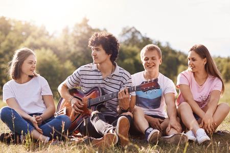 Vrienden die graag liedjes zingen, samen tijd doorbrengen, een goed humeur hebben, iemands verjaardag vieren, een zonnige zomerdag doorbrengen met vrienden, een gelukkige gezichtsuitdrukking hebben. Vriendschap en mensenconcept Stockfoto