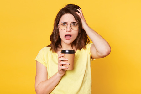 Emotional stunned woman with pleasant appearance stares with eyes popped out, dressed casually,holding takeaway cup of hot beverage, stands against yellow background. Youth and drinking concept. Stock Photo