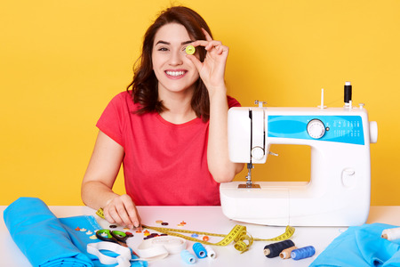 Young creative women in studio, has dark hair, wearing red casual t shirt, sits smiling at table in atelie near sewing equipments, covers eye with botton, startup business concept, yellow background.