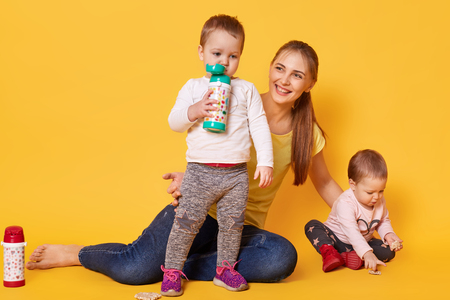 Image of loving attractive mother looks after her little children, twins playing with mommy. Playful kids drink tasty baverage from her bootle while her sister eating coockies. Infants are hungry. Banque d'images